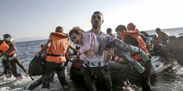 A Syrian migrant holds a young girl in his arms upon arriving on a dinghy to the Greek island of Kos, Greece.(EPA/Yannis Kolesidis)