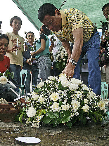 Mayor Duterte placing flowers at the Davao International Airport in 2009 to commemorate the 6-year anniversary of the bombing there. Photo Credit: Kieth B. via Flickr.
