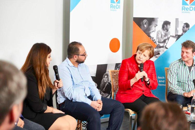 Chancellor Merkel speaking with Luna Benndakji