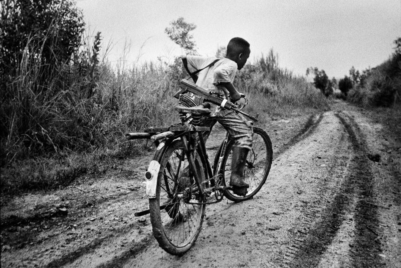 A child soldier rides back to his base in Ituri district, northeastern Congo. 2003