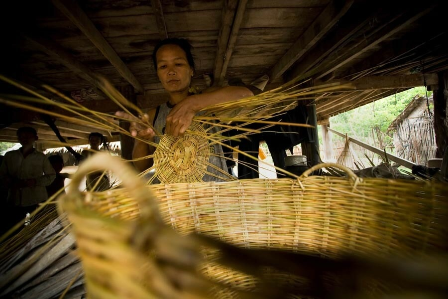 24 June 2006, Pursat - A woman weaving baskets under the house in Thkaol Thom Village in Pursat Province. The baskets are used to transport fish and are sold for about USD $1 for a medium sized one such as this. FAO project SPFP/CMB/6701 - SPFP Cambodia. Within the framework of the Strategy for National Agricultural Development: Horizon 2010 and in line with the specific objectives of the FAO Special Programme for Food Security, the objective of the SPFS programme of Cambodia is: To maximize national food self-reliance and to reduce the risks of disruptive variations in supply by demonstrating and facilitating a rapid increase in agricultural productivity and food production on an economically and environmental sustainable basis. More specifically the immediate objectives of the pilot phase of the SPFS will be to assist the Government of Cambodia: To identify and demonstrate appropriate technologies to better control water for agricultural production, to intensify production through improved varieties, soil fertilization and integrated pest management and to diversify farm income through small livestock and aquaculture improvements; Through a participatory process identify farmers requirements and constraints in the introduction of the technologies and in the establishment of active community participation in the operation and maintenance of the common resource base and water control system; Through an intensive staff training programme to create an effective local capability to provide the essential support services and to assist farmers in the introduction of the improved agricultural technologies; To prepare recommendations to extend the pilot demonstrations into national and regional action programmes linked to international aid and lending programmes.