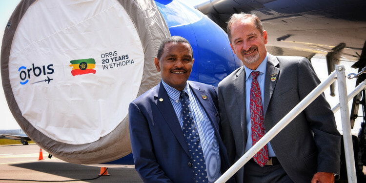 Orbis Flying Eye Hospital Program  Addis Ababa, Ethiopia - October 1 - 19, 2018 Sponsored by the Alcon Foundation -- Bob Ranck and the Honorable Dr. Kebede Worku, State Minister, Federal Minister of Health on the steps of the FEH at Bole International airport after the Opening Ceremony to kick off the program.