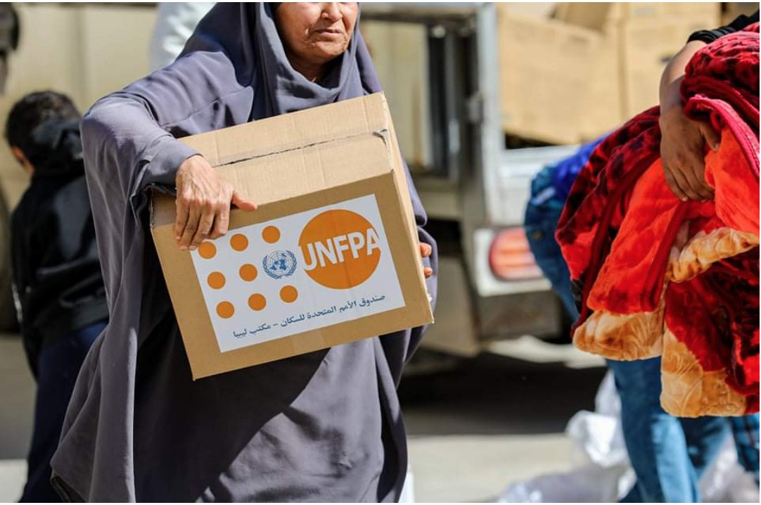 A woman, internally-displaced by the conflict in Tripoli, holds a dignity kit containing essential items for her hygiene.