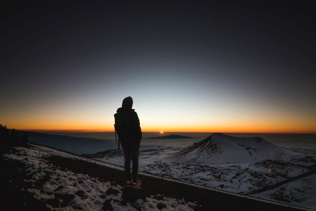 Hiker facing the expansive horizon in Mauna Kea, U.S