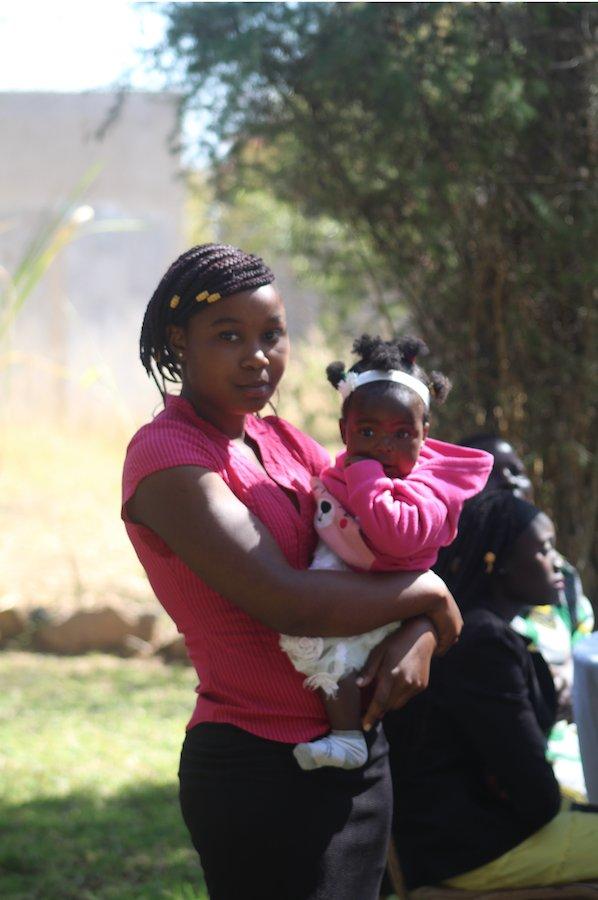 Ruth Musarurwa poses holding her baby, Seke teen mother