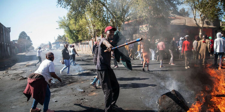 A man holds a stick in front of burning furniture in the streets during riots in Johannesburg, SA.   Credit: Getty Images