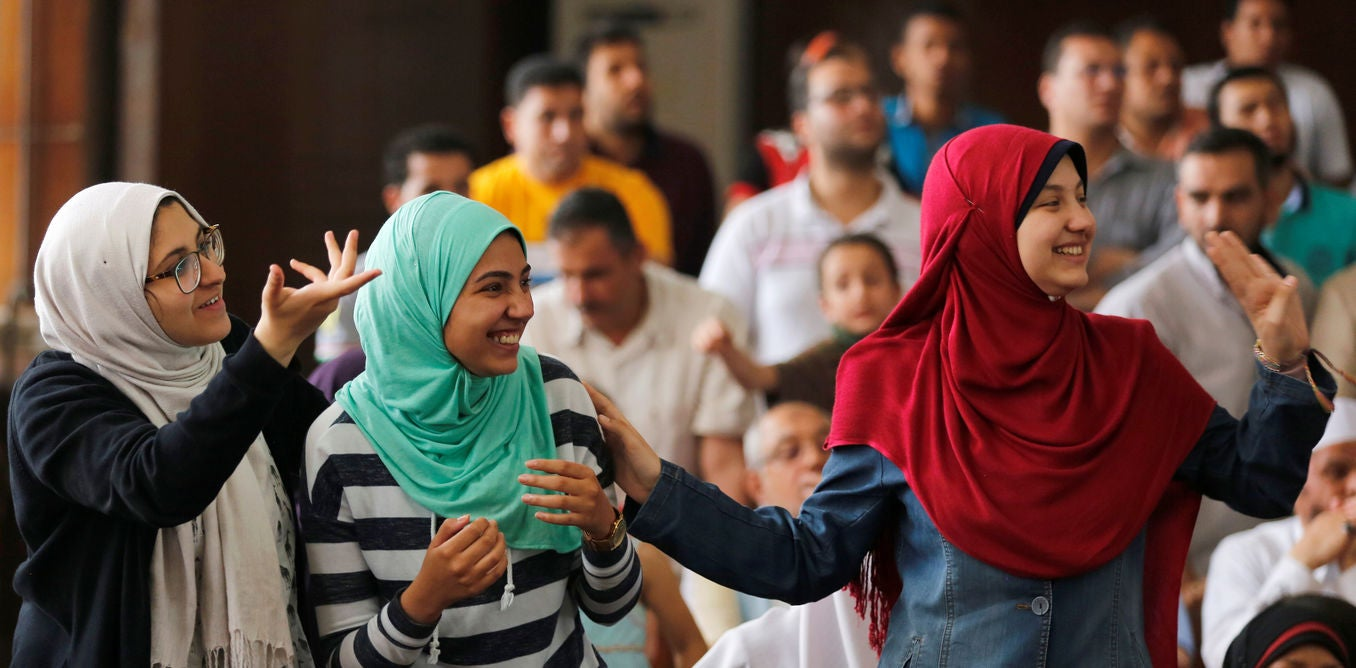 Family members and relatives of Muslim Brotherhood members, on trial for an armed sit-in at Rabaa square, wave and cheer them on at a court on the outskirts of Cairo, Egypt May 31, 2016. Credit: Reuters