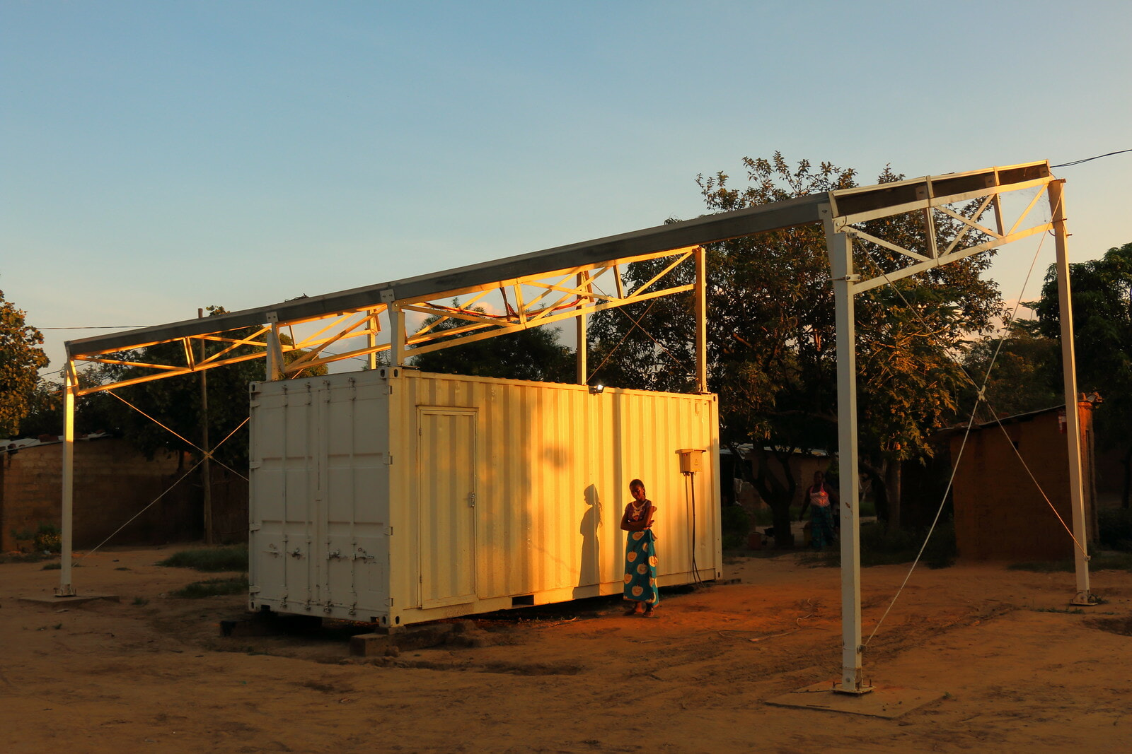 Woman in rural Tanzania standing next to a solar home system
