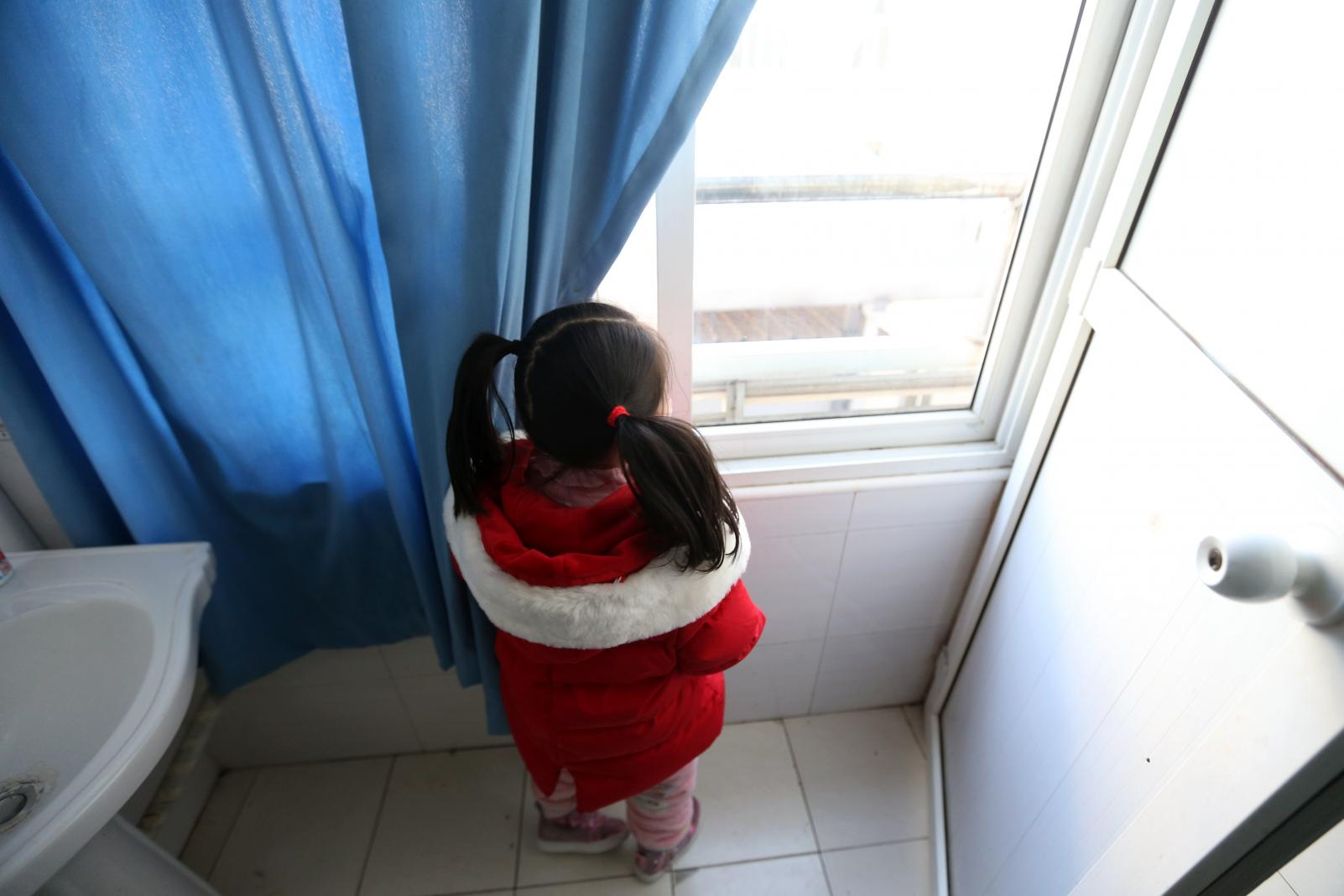 A child looking out the window, unable to go outside to play.