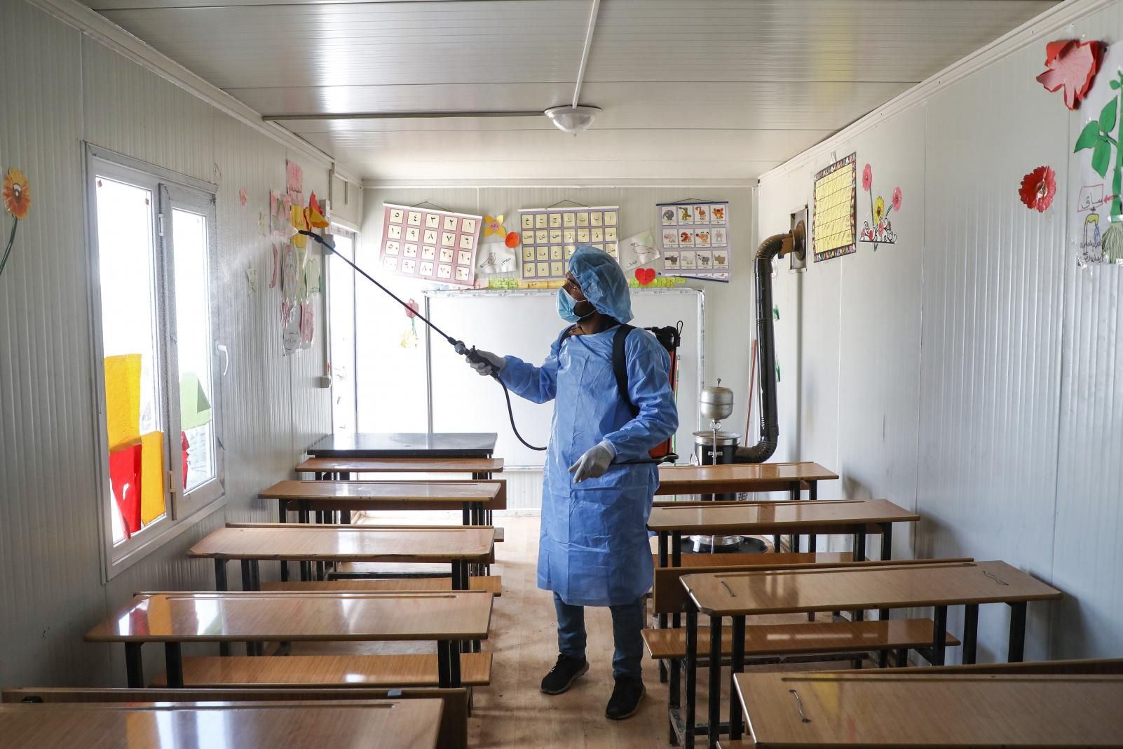 A man disinfecting an empty classroom once the school was closed.
