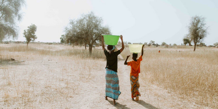 Women carrying water home from the well in Linguere, Senegal.